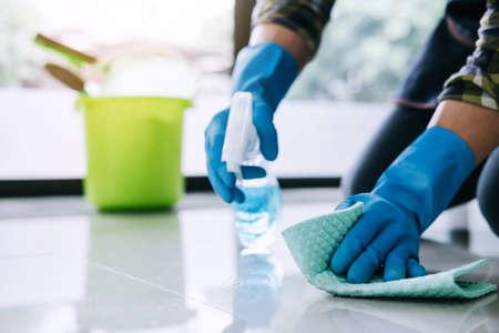 Concetto di pulizia e pulizia del marito, giovane felice in guanti di gomma blu che puliscono la polvere usando uno spray e uno spolverino mentre puliscono il pavimento a casa. Archivio Fotografico