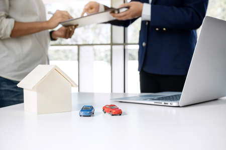 Car and Home for rent concept, broker agent presenting and consult to customer to decision making sign form agreement, home and car model. 스톡 콘텐츠
