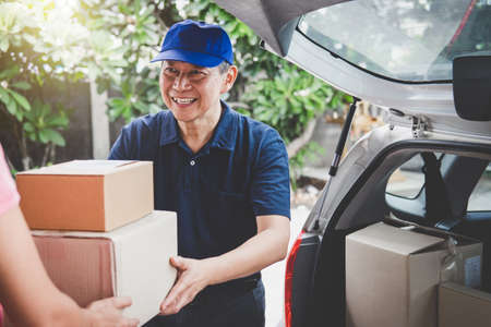 Home delivery service and working service mind, Woman customer hand receiving a cardboard boxes parcel from delivery service courier. Stock Photo