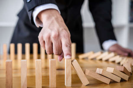 Wooden game strategy, Businessman hand stopping falling wooden dominoes effect from continuous toppled or risk, strategy and successful intervention concept for business. Stock Photo