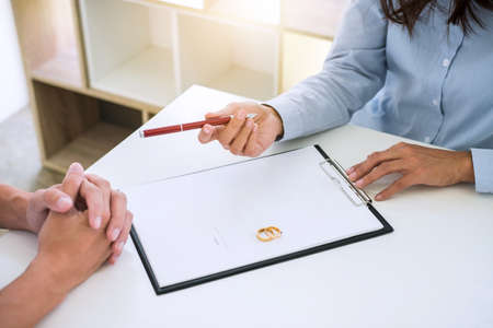 Husband and wife are reading divorce agreement and filing pen to signing decree of divorce (dissolution or cancellation) of marriage filing divorce papers and two golden marry ring. Reklamní fotografie