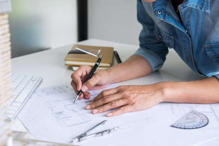 Architect working on blueprint, Engineer working with engineering tools for architectural project on workplace, Construction concept - building project, blueprints, ruler and dividers. Archivio Fotografico