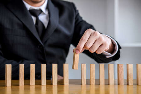 Wooden game strategy, Risk and strategy in business, Close up of businessman hand gambling placing wooden block on a line of domino. Stock Photo