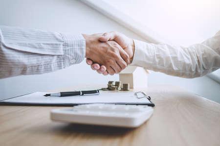 Agente de corredor de bienes raíces y cliente dándose la mano después de firmar los documentos del contrato para la compra de bienes raíces de propiedad, aprobación de préstamo hipotecario de concepto.