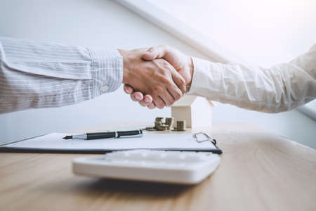 Agente di mediatore immobiliare e cliente si stringono la mano dopo aver firmato i documenti contrattuali per l'acquisto di immobili di proprietà, approvazione del mutuo ipotecario di concetto.