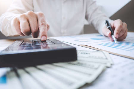 Finances Saving Banking Concept, Man accountant calculations income and analyzing financial graph data with calculator. Stock Photo