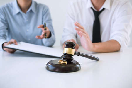Contract decree of divorce (dissolution or cancellation) of marriage, husband and wife during divorce process and signing of divorce contract, Wedding ring. Stock Photo