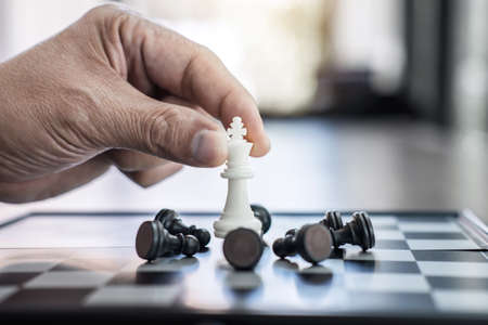 Hands of confident businessman colleagues playing chess game to development analysis new strategy plan, leader and teamwork concept for win and success.