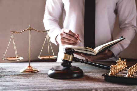 Młotek na drewnianym stole i prawnik lub sędzia pracujący z umową w temacie sali sądowej, koncepcja sprawiedliwości i prawa.