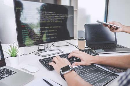 Los programadores que cooperan en el desarrollo de la programación y el sitio web que trabajan en un software desarrollan la oficina de la empresa, escriben códigos y escriben códigos de datos. Foto de archivo