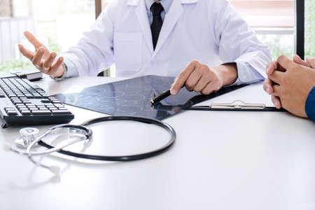 El profesor médico recomienda informar un método con el tratamiento del paciente, los resultados al examinar una película de rayos X del cerebro con imagen sobre el problema del paciente mientras trabaja en la oficina.