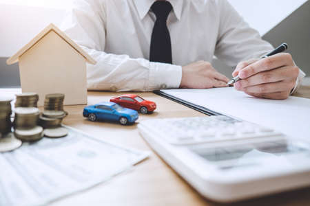 Businessman working doing finances and calculation cost of real estate investment while be signing to contract, Concept mortgage loan approval. Stock Photo