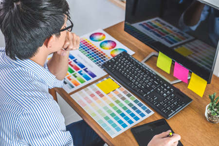 Image of male creative graphic designer working on color selection and drawing on graphics tablet at workplace with work tools and accessories in workspace. 版權商用圖片