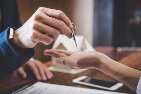 Agente immobiliare Responsabile delle vendite che detiene le chiavi del deposito al cliente dopo aver firmato il contratto di locazione di affitto del contratto di compravendita, relativo all'offerta di mutuo ipotecario e all'assicurazione sulla casa. Archivio Fotografico