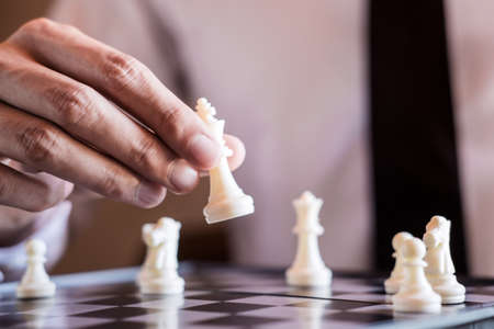 Hand of confident businessman use king chess piece white playing chess game to development analysis new strategy plan, business strategy for win and success.