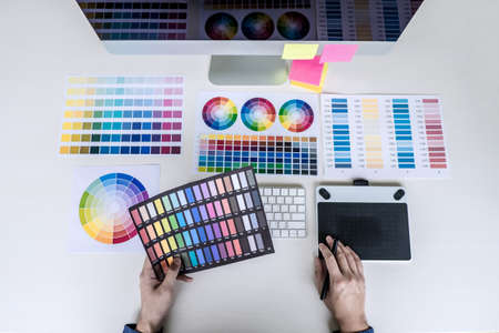 Male creative graphic designer working on color selection and color swatches, drawing on graphics tablet at workplace with work tools and accessories, top view workspace.