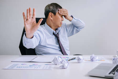 Feeling sick and tired, Senior businessman depressed and exhausted, businessman at his desk frustrated with problems with a pile of work and keeping eyes closed while sitting on office.
