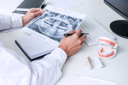 Male doctor or dentist writing report working with tooth x-ray film, model and equipment used in the treatment of dental and dentistry at workplace. Stock Photo