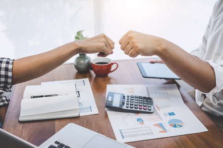 Teamwork of businesspeople partnership giving fist bump to greeting start up business strategy project. Banco de Imagens