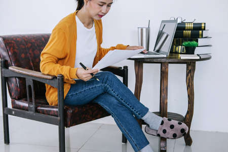 Happy casual young asian woman working in home or small office with using a laptop and document report on desk as a freelancer.
