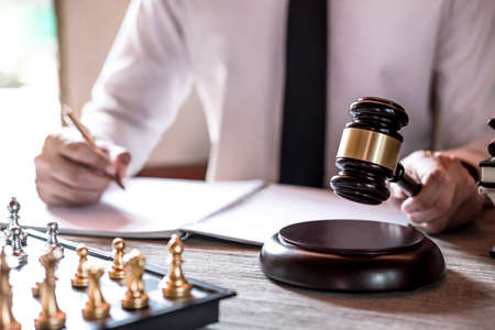 Legal law, advice and justice concept, Professional male lawyers working on courtroom sitting at the table and signing papers with gavel and Scales of justice. Stok Fotoğraf