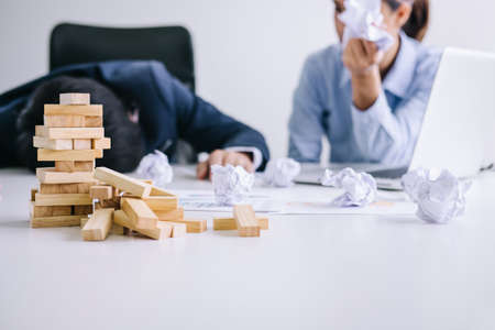 Boss and executive team feeling stress and serious of fail business, partners holding heads in hands depressed by failure and exhausted with problems with a pile of work.