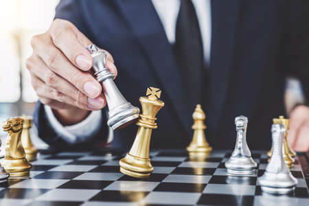 Businessman playing chess game reaching to plan strategy for success, thinking for planning overcoming difficulty and achieving goals business strategy for win, management or leadership concept.