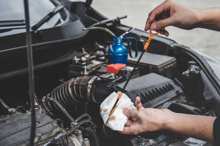 Services car engine machine concept, Automobile mechanic repairman hands checking a car engine automotive with oil level in the engine transportation, car service and maintenance. 版權商用圖片