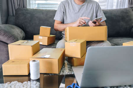 Small business parcel for shipment to client at home, Young entrepreneur SME freelance man working online business by using smart phone with making on purchase order and preparing package product. Banque d'images - 118104561