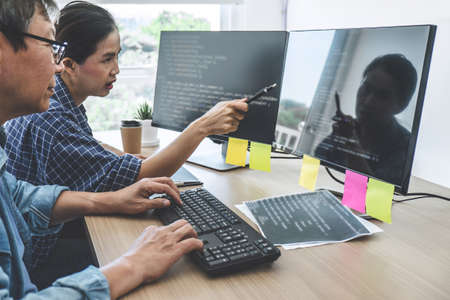Two professional programmers cooperating at Developing programming and website working in a software develop company office, writing codes and typing data code.