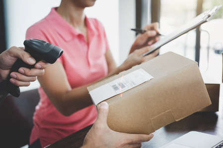 Home delivery service and working service mind, deliveryman working barcode scan checking order to confirm sending customer in post office. 版權商用圖片 - 119796058