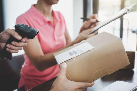 Servicio de entrega a domicilio y mente de servicio de trabajo, el repartidor que trabaja con el escaneo de código de barras revisa el pedido para confirmar el envío del cliente en la oficina de correos.