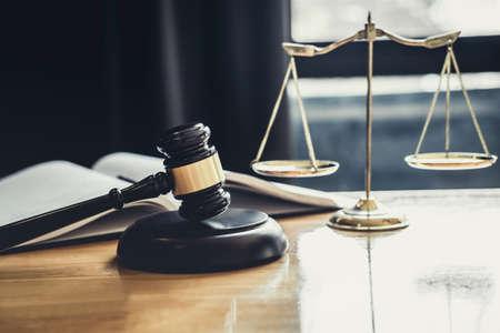 Sędzia młotek ze skalą sprawiedliwości, dokumenty przedmiotowe pracujące na stole w sali sądowej, porady prawne i koncepcja sprawiedliwości.