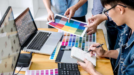 Team of young colleagues creative graphic designer working on color selection and drawing on graphics tablet at workplace, Color swatch samples chart for selection coloring. 版權商用圖片