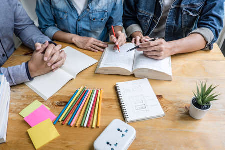 Education, teaching, learning concept. High school students or classmates group tutor in library studying and reading with helps friend doing homework and lesson practice preparing exam to entrance.