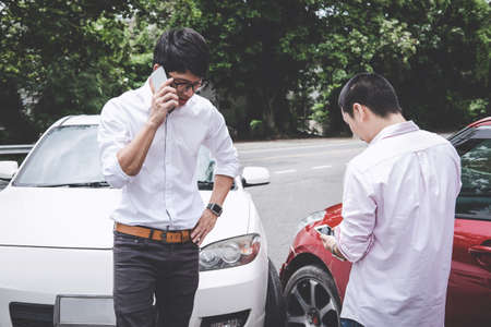 Two drivers man arguing after a car traffic accident collision and making phone call to Insurance Agent, Traffic Accident and insurance concept. Reklamní fotografie