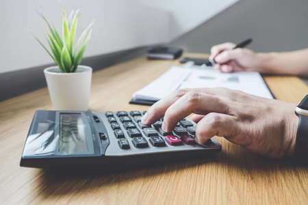 Businessman working on a graph document financial report and analysis calculation investment cost with calculator at office desk and other objects around.