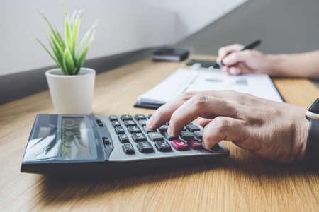 Zakenman die aan een financieel rapport van het grafiekdocument werkt en de investeringskosten van de analyseberekening met calculator bij bureau en andere voorwerpen rond.
