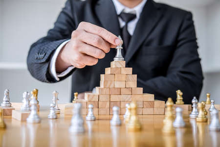 Wooden game of strategy, Hands of confident businessman playing chess game to development analysis new strategy plan, leader and teamwork concept for win and success.