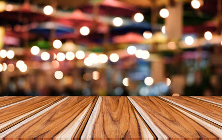 Selective Empty wooden table in front of abstract blurred festive light background with light spots and bokeh for product montage display of product. Stock Photo