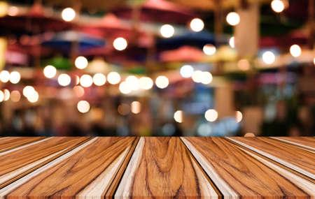 Tavolo in legno vuoto selettivo davanti a uno sfondo luminoso festivo sfocato astratto con punti luce e bokeh per la visualizzazione del montaggio del prodotto. Archivio Fotografico