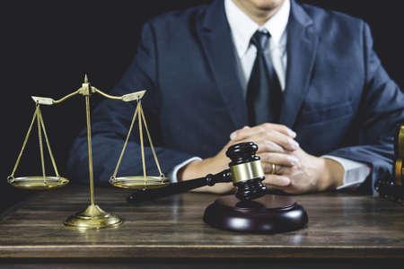 Consigliere o avvocato maschio che lavora in aula seduto al tavolo. Diritto legale, martelletto del giudice con consulenza degli avvocati della giustizia con martelletto e bilancia della giustizia.