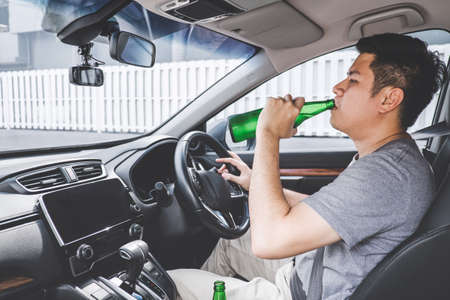 Young asian man drives a car with drunk a bottle of beer behind the wheel of a car.