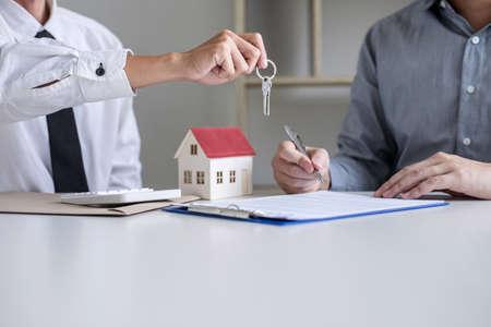 Nieruchomości Kierownik sprzedaży wydający klucze klientowi po podpisaniu umowy najmu dzierżawy umowy kupna sprzedaży, dotyczącej oferty kredytu hipotecznego i ubezpieczenia domu. Zdjęcie Seryjne