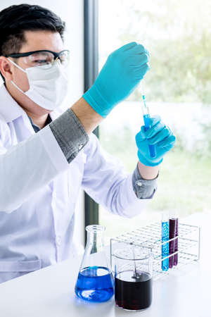 Biochemistry laboratory research, Chemist is analyzing sample in laboratory with equipment and science experiments glassware containing chemical liquid.