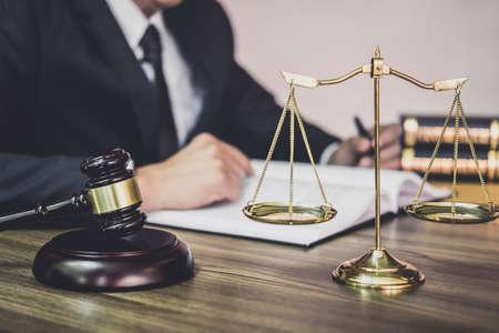 Le juge gavel avec des avocats de la justice, Gavel sur une table en bois et un conseiller ou un avocat travaillant sur des documents dans un cabinet d'avocats en fonction. Concept de droit juridique, de conseil et de justice.