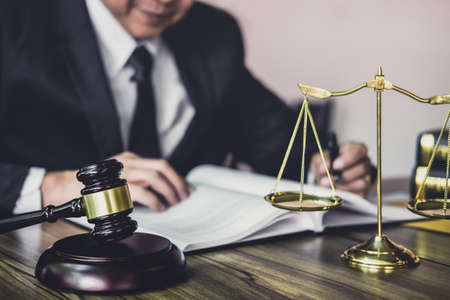 Judge gavel with Justice lawyers, Gavel on wooden table and Counselor or Male lawyer working on a documents. Legal law, advice and justice concept. Stock Photo