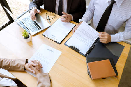 Two selection committee manager reading a resume during a job interview, Employer interviewing to ask young female job seeker for recruitment talking in office.
