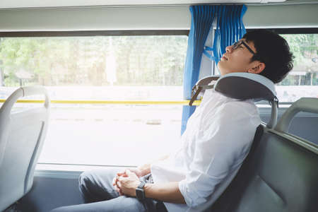 Young Asian man traveler sitting on a bus and sleeping with pillow, transport, tourism and road trip concept.