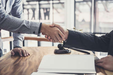 Handshake after good cooperation, Businessman Shaking hands with Professional male lawyer after discussing good deal of contract in courtroom. Stock Photo